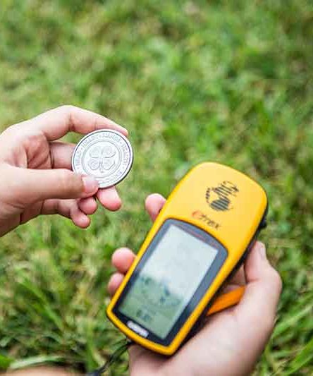 child holding a coin with a 4-H logo and a Garmin GPS navigator